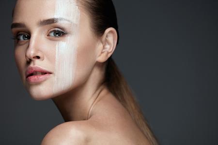 Soin de la peau. Gros plan du beau modèle féminin jeune avec une peau pure et un maquillage professionnel naturel. Portrait de femme sexy avec un rayon de masque de crème de teinte de peau sur le visage. Visage beauté. Haute résolution