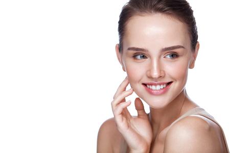 Schoonheid Cosmetica. Close-up Aantrekkelijk Jong Vrouwelijk Model met Verse Natuurlijke Make-up wat betreft Haar Zachte Vlotte Zuivere Huid. Mooie lachende vrouw poseren op witte achtergrond. Huidsverzorging. Hoge resolutie