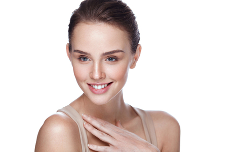 Beauty Cosmetics. Closeup Attractive Young Female Model With Fresh Natural Makeup Touching Her Soft Smooth Pure Skin. Beautiful Smiling Woman Posing On White Background. Skin Care. High Resolution