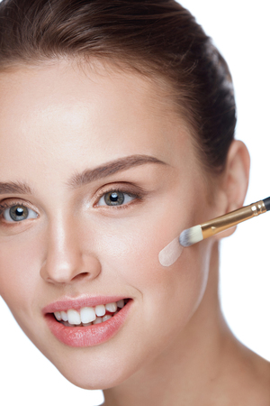 Beauty Cosmetics. Portrait Of Beautiful Young Woman Applying Foundation On Face With Cosmetic Brush. Closeup Of Attractive Female With Smooth Skin And Natural Makeup. Facial Care. High Resolution