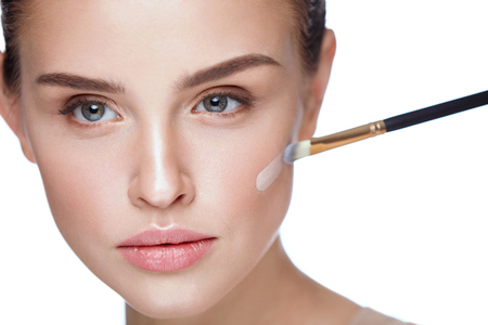 Woman Beauty Face Makeup. Portrait Of Beautiful Young Female Applying Foundation On Face With Cosmetic Brush. Closeup Of Attractive Girl With Smooth Skin And Natural Makeup. Cosmetics. High Resolution