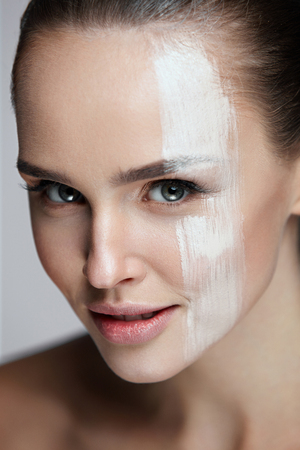 Beauty Cosmetics. Portrait Of Attractive Sexy Girl With Foundation Line On Face. Closeup Of Beautiful Young Woman With Sexy Makeup And Cream Mask On Smooth Skin. Facial Care. High Resolution