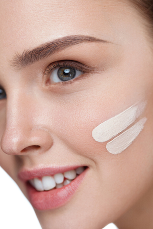 Facial Makeup. Closeup Of Skin Tone Cream Lines On Beautiful Sexy Young Woman Face. Attractive Healthy Female Model With Pure Soft Skin And Fresh Professional Make-Up. Cosmetics. High Resolution Stock Photo