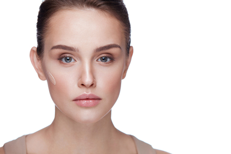 Beauty Cosmetics. Closeup Of Beautiful Young Female Model With Line Of Foundation Cream On Face. Portrait Of Attractive Woman With Fresh Skin And Professional Makeup. Facial Care. High Resolution Stock Photo
