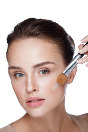 Beauty Cosmetics. Closeup Of Attractive Sexy Female Model Applying Cream Foundation With Brush On Face. Portrait Of Beautiful Young Woman With Fresh Skin And Perfect Natural Makeup. High Resolution Stock Photo