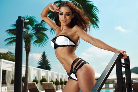 Fashion Women Swimwear. Beautiful Woman Model With Fit Sexy Body, Tanned Skin In Stylish Fashionable White Black Bikini, Sky On Background. Hot Girl At Luxury Resort Hotel In Summer. High Resolution