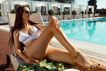 female model: Sexy Woman In Bikini Sunbathing Near Swimming Pool In Summer. Beautiful Female Model With Hot Fit Body, Long Legs In Fashionable Swimwear, Fashion Sunglasses Relaxing At Poolside At Luxury Resort
