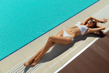 Beautiful Woman With Sexy Fit Body In Fashion Bikini Relaxing At Swimming Pool Edge. Female With Long Legs, Healthy Skin Tan In Fashionable White Swimwear, Sunglasses Sunbathing At Poolside In Summer