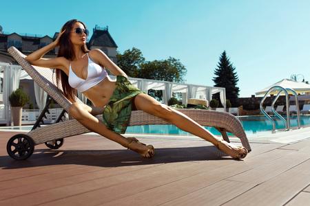 フィットのボディを持つ美しいセクシーな女性の長い脚、エレガントな白ビキニで健康的な日焼け肌ファッショナブルなサングラスにバカンス リゾ