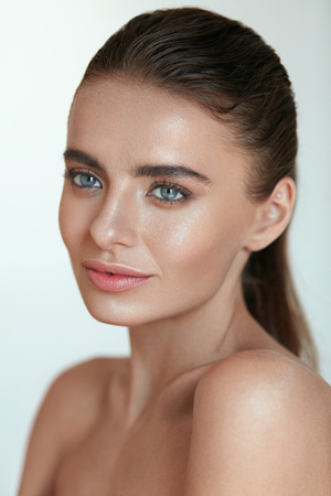 skin care woman: Portrait Of Beautiful Young Female Model With Highlighter On Facial Skin