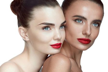 Frau Schönheit Gesichter. Weibliche Modelle mit Glamour Gesichts Make-up, frische weiche gesunde Haut und glamouröse rote Lippen. Closeup Portrait der schönen sexy junge Mädchen posiert auf weißem Hintergrund. Hohe Auflösung Standard-Bild