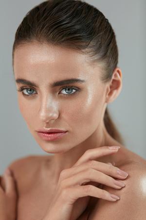 회색 배경에 부드러운 신선한 빛나는 피부를 만지는 아름 다운 섹시 한 소녀.