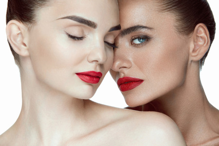 sexy young girls: Fashion Makeup. Portrait Of Two Attractive Sexy Girls With Fashionable Makeup And Red Lips. Closeup Of Fashionable Young Women With Fresh Soft Smooth Skin Posing On White Background. High Resolution