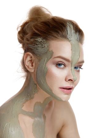 Cuidado de la piel y el cuerpo. Primer plano de hermosa mujer sexy con máscara de arcilla cosmética en la piel. Retrato de mujer joven y saludable con maquillaje natural fresco. Spa Cosmetics. Alta resolución