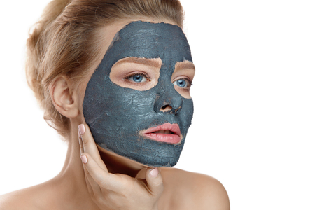 Closeup Of Healthy Beautiful Female With Natural Makeup Applying Grey Clay Mask On Face. Stock Photo