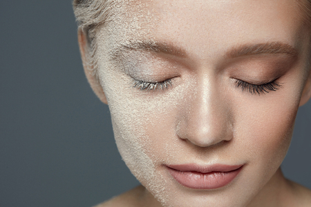 Belleza Maquillaje Cosméticos. Closeup Atractiva Cara Joven Cubierto Con La Fundación De Polvo Suave Cosmética. Retrato Del Modelo Femenino Atractivo Hermoso Con El Maquillaje Natural Y La Piel Suave. Alta resolución