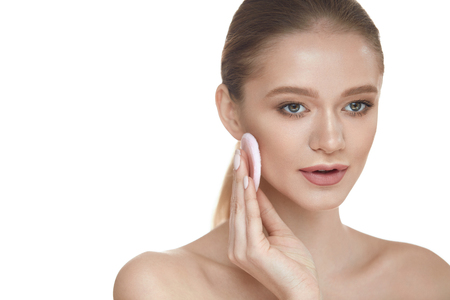 Portrait Of Young Beautiful Woman With Powder Cushion Puff Applying Cosmetic Powder On Face. Stock Photo