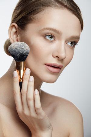 Portrait Of Beautiful Woman With Powder Brush On White Background. Stock Photo