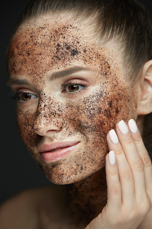 Face Care. Closeup Of Beautiful Woman With Natural Makeup And Skin Exfoliating Coffee Scrub On Beauty Face. Attractive Young Female Applying Mask, Doing Skin Peeling Spa Procedure. High Resolution Фото со стока - 78817178