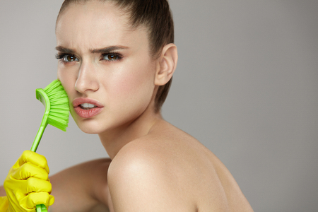 pulizia viso: Beauty Face Skin Care. Closeup Young Woman In Yellow Gloves And Cleaning Brush In Hand Exfoliating Skin. Portrait Of Beautiful Healthy Girl With Natural Makeup Scrubbing Facial Skin. High Resolution Archivio Fotografico