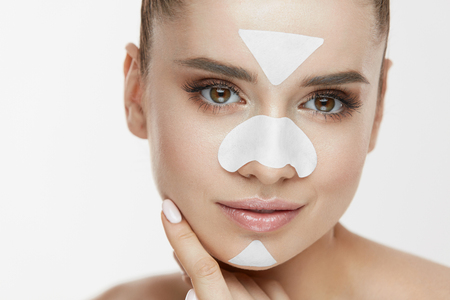 Beauty Cosmetics. Young Female With Cleansing Patches On Skin Touching Face. Closeup Of Attractive Girl With Fresh Natural Makeup And Facial Mask Strips On Nose, Chin And Forehead. High Resolution Stock Photo - 78817182