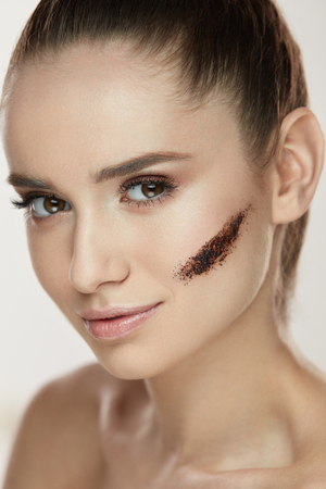 Beauty Cosmetics. Closeup Of Healthy Young Woman With Stripe Of Coffee Scrub Mask On Facial Skin. Portrait Of Beautiful Female With Pure Soft Skin And Fresh Makeup. Face Skin Care. High Resolution Stock Photo