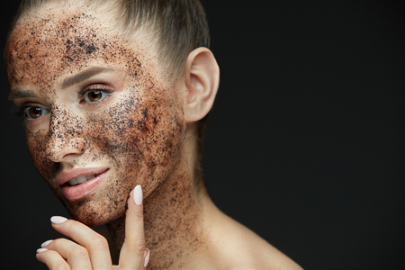 Face Care. Closeup Of Beautiful Woman With Natural Makeup And Skin Exfoliating Coffee Scrub On Beauty Face. Attractive Young Female Applying Mask, Doing Skin Peeling Spa Procedure. High Resolution