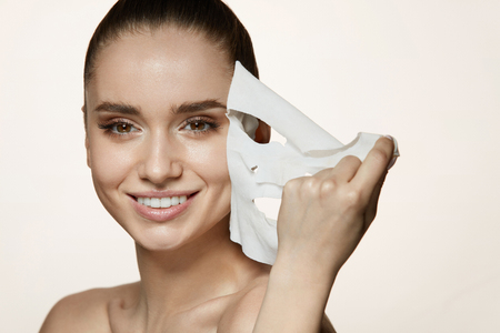 Woman Beauty Face. Closeup Of Smiling Young Female With Fresh Natural Makeup Removing Textile Sheet Mask From Facial Skin. Portrait Of Attractive Happy Girl With White Cosmetic Mask. High Resolution Archivio Fotografico