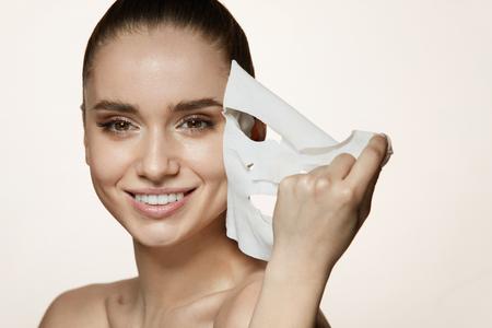 Vrouw schoonheid gezicht. Close-up van glimlachend jong wijfje met verse natuurlijke make-up die textielbladmasker verwijderen uit gezichtshuid. Portret van aantrekkelijke gelukkig meisje met witte cosmetische masker. Hoge resolutie Stockfoto