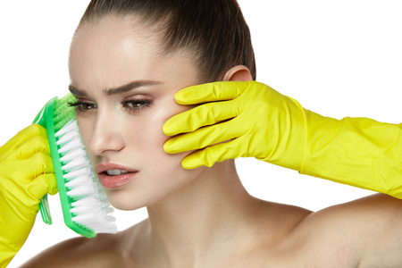 Facial Skin Care. Portrait Of Beautiful Young Woman With In Gloves Scrubbing Face With Brush. Closeup Of Grimaced Sexy Female Model With Fresh Makeup And Soft Skin. Cosmetology. High Resolution Stock Photo