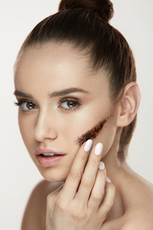 Beauty Treatment. Portrait Of Young Woman Applying Coffee Scrub On Facial Skin. Closeup Of Beautiful Sexy Girl With With Fresh Makeup And Stripe Of Cosmetic Mask On Face. Cosmetology. High Resolution