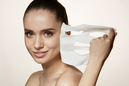 Face Skin Care. Portrait Of Beautiful Smiling Girl Removing White Sheet Mask From Healthy Fresh Skin. Closeup Of Attractive Sexy Woman With Natural Makeup And Mask On Facial Skin. High Resolution