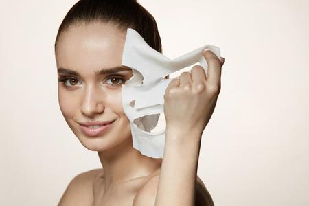 顔のスキンケア。健康な新鮮な皮膚から白いシート マスクを除去する美しい笑みを浮かべて少女の肖像画。自然化粧品と肌にマスクで魅力的なセク 写真素材