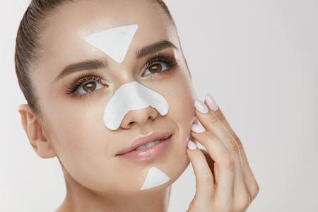 美容化粧品。若い女性の顔に触れる皮膚にパッチをクレンジングします。新鮮な自然化粧や鼻、あご、額に顔マスク ストリップと魅力的な女の子の