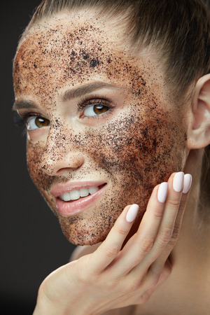 Face Care. Closeup Of Beautiful Woman With Natural Makeup And Skin Exfoliating Coffee Scrub On Beauty Face. Attractive Young Female Applying Mask, Doing Skin Peeling Spa Procedure. High Resolution Фото со стока - 78817209