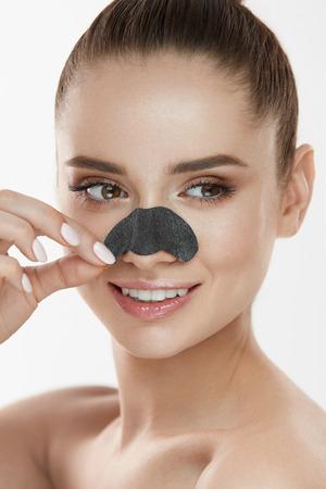 뷰티 스킨 케어. 얼굴 피부에 검은 코 패치를 적용하는 아름 다운 섹시 한 소녀. 근접 촬영 젊은 여성 모델 신선한 자연 메이크업 및 부드러운 부드러운 스톡 콘텐츠