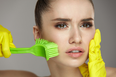 Beauty Face Skin Care. Closeup Young Woman In Yellow Gloves And Cleaning Brush In Hand Exfoliating Skin. Portrait Of Beautiful Healthy Girl With Natural Makeup Scrubbing Facial Skin. High Resolution Фото со стока