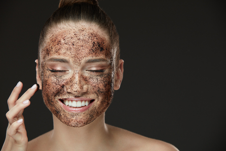 Esfregar la piel de la cara. Retrato De Sexy Modelo Femenino Sonriente Aplicando Máscara De Café Natural, Exfoliante En La Piel Facial. Primer De La Mujer Feliz Hermosa Con La Cara Cubrió Con El Producto De La Belleza. Alta resolución
