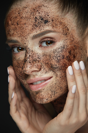 Beauty Face Care. Portrait Of Attractive Young Woman Putting Coffee Scrub On Facial Skin. Closeup Beautiful Sexy Female Model Touching Face With Hands, Exfoliating And Scrubbing Skin. High Resolution Фото со стока - 78817319