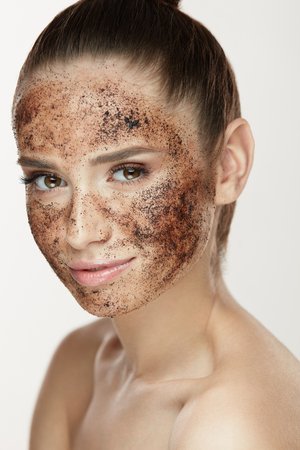 Face Care. Closeup Of Young Woman With Natural Makeup And Coffee Scrub Mask On Fresh Facial Skin. Portrait Of Beautiful Sexy Female Model With Peeling Cosmetic Product On Beauty Face. High Resolution Фото со стока