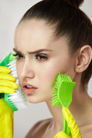 Facial Peeling. Portrait Of Attractive Young Female Model Peels Facial Skin With Two Cleansing Brushes. Closeup Of Beautiful Woman With Natural Makeup And Soft Skin Exfoliating Face. High Resolution