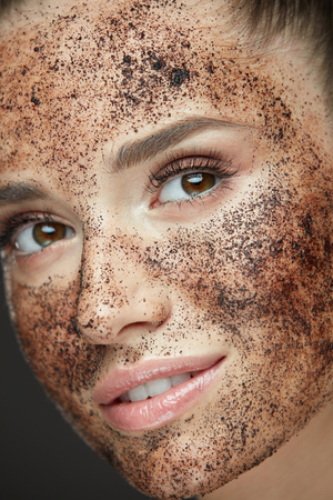 Woman Beauty Face. Closeup Of Beautiful Young Female Model With Fresh Coffee Mask, Face Scrub On Skin. Sexy Healthy Girl With Natural Makeup Exfoliating Skin With Skin Care Cosmetics. High Resolution