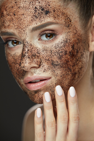 Face Care. Closeup Of Beautiful Woman With Natural Makeup And Skin Exfoliating Coffee Scrub On Beauty Face. Attractive Young Female Applying Mask, Doing Skin Peeling Spa Procedure. High Resolution Фото со стока - 78817371