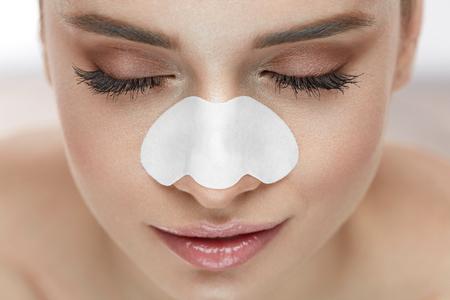 鼻の上の皮膚ケア パッチで美人顔。新鮮なきれいな肌の気孔帯をクレンジングで若い女性の肖像画。自然化粧品と美容製品でセクシーな女の子のク