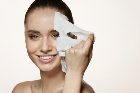 Frau Schönheitsgesicht. Nahaufnahme des lächelnden jungen Weibchens mit frischem natürlichem Make-up, das Textilblattmaske von der Gesichtshaut entfernt. Porträt des attraktiven glücklichen Mädchens mit weißer kosmetischer Maske. Hohe Auflösung
