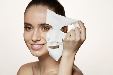 Frau Schönheit Gesicht. Nahaufnahme des lächelnden jungen weiblichen mit frischen natürlichen Make-up entfernen Textil-Blatt-Maske aus Gesichts-Haut. Porträt von attraktiven glücklichen Mädchen mit weißen kosmetischen Maske. Hohe Auflösung