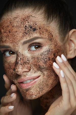 Beauty Face Care. Portrait Of Attractive Young Woman Putting Coffee Scrub On Facial Skin. Closeup Beautiful Sexy Female Model Touching Face With Hands, Exfoliating And Scrubbing Skin. High Resolution Фото со стока