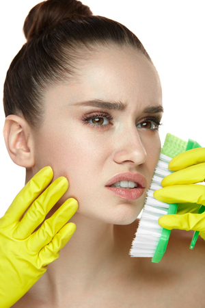 Facial Skin Care. Portrait Of Beautiful Young Woman With In Gloves Scrubbing Face With Brush. Closeup Of Grimaced Sexy Female Model With Fresh Makeup And Soft Skin. Cosmetology. High Resolution Фото со стока