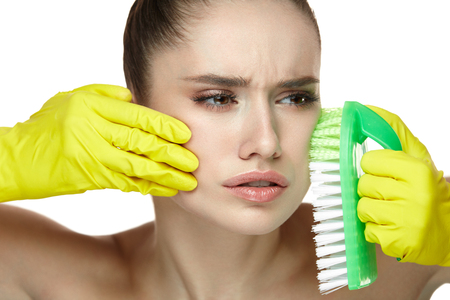 Facial Skin Care. Portrait Of Beautiful Young Woman With In Gloves Scrubbing Face With Brush. Closeup Of Grimaced Sexy Female Model With Fresh Makeup And Soft Skin. Cosmetology. High Resolution Фото со стока - 78817394
