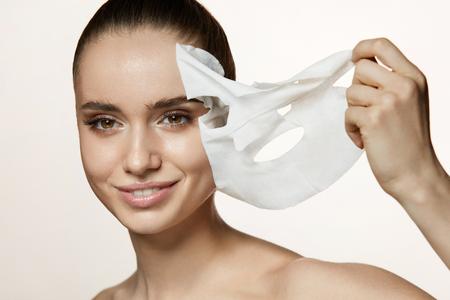 스킨 케어 스킨. 건강 한 신선한 피부에서 흰색 시트 마스크를 제거하는 아름 다운 웃는 소녀의 초상화. 매력적인 메이크업 및 얼굴 피부에 마스크와  스톡 콘텐츠